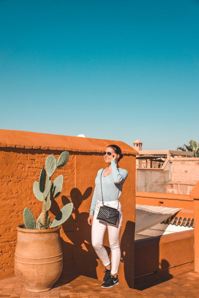 Standing on a rooftop in a Moroccan Riad, enjoying the sun on a sunny day in Marrakech.
