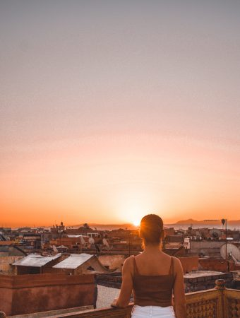 Standing on a rooftop in a Moroccan Riad, watching the sun rise over Marrakech.